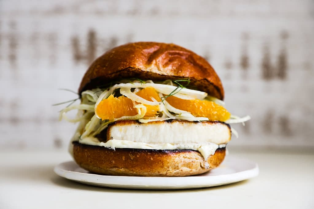 A grilled swordfish sandwich piled high with shaved fennel and orange salad.