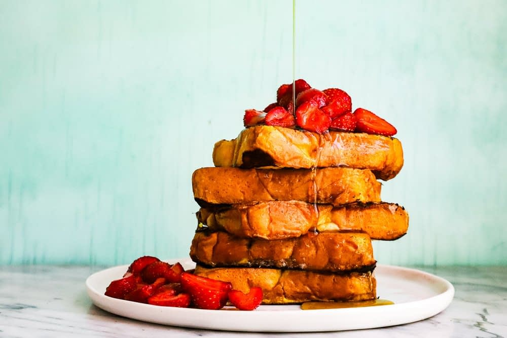 A stack of french toast piled high with strawberries.