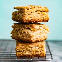 Flaky biscuits stacked high on a cooling rack.