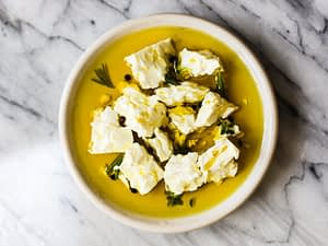Chunks of marinated feta in olive oil and herbs.