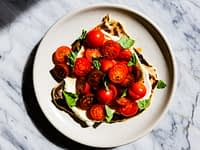 Tomatoes and ricotta on a sourdough flatbread, on a plate, on a marble surface,