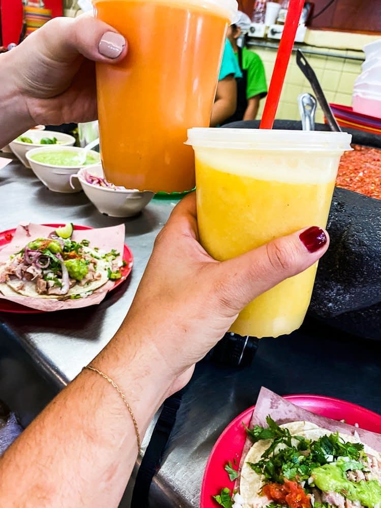 Two brightly-colored fruit juices held in the air by two hands over a restaurant counter with tacos on it.