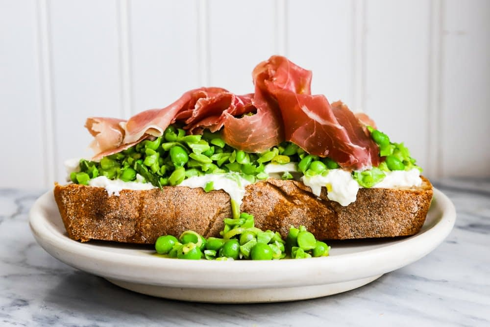A thick piece of toast piled high with burrata, peas and prosciutto.