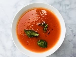 A bowl of tomato soup with basil and olive oil.
