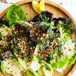 A Caesar salad on a wood plate on a wood surface.